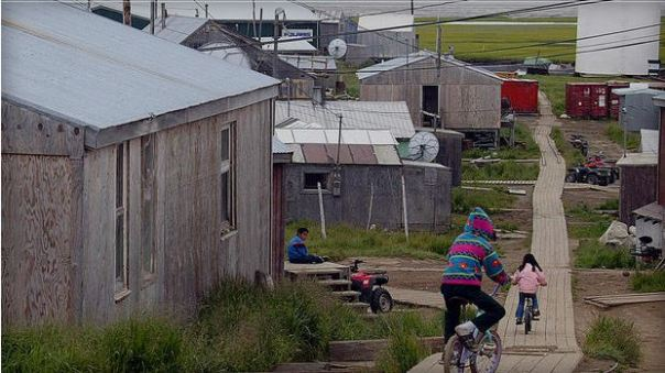 Children ride their bikes along the board walk in Hooper Bay, Alaska, July 11, 2003.  CBS News.