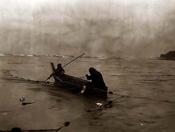 Quinalt members fishing from canoe using nets. Photo by Edward S Curtis.